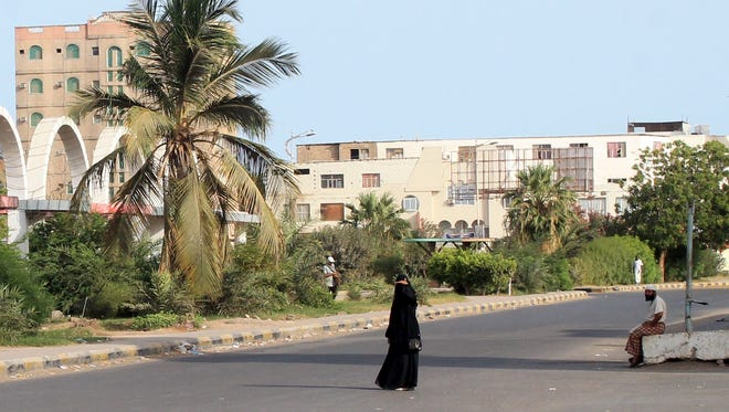 People walk on an empty road  in the southern Yemeni port city of Aden, on May 13, 2015, the first day of a humanitarian pause in a Saudi-led bombing campaign against Houthi rebels.