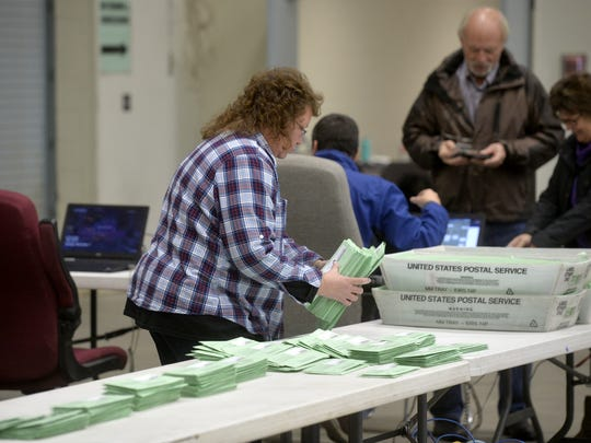 Teri March collects mail-in ballots for counting on Tuesday afternoon at the polling head quarters in Exhibition Hall.