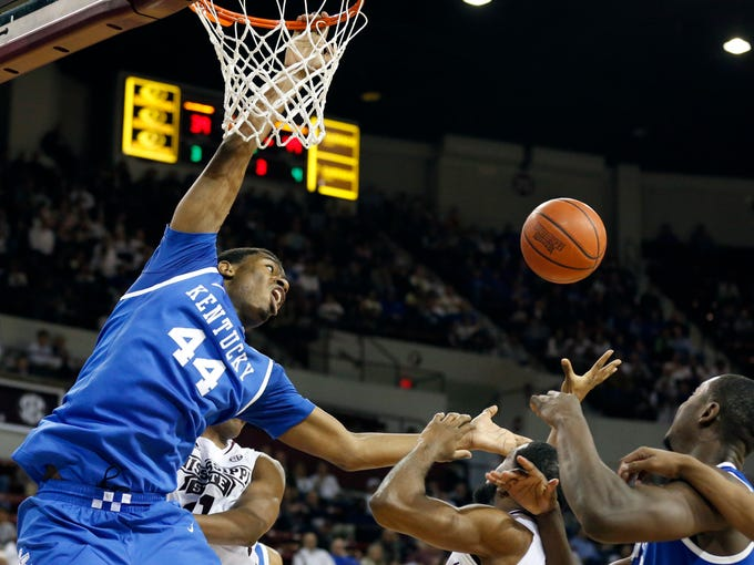 Kentucky center Dakari Johnson (44) reaches for a loose ball as he clings to the rim in the second half of an NCAA college basketball game against Mississippi State  in Starkville, Miss., Saturday, Feb. 8, 2014.  Kentucky won 69-59. (AP Photo/Rogelio V. Solis)