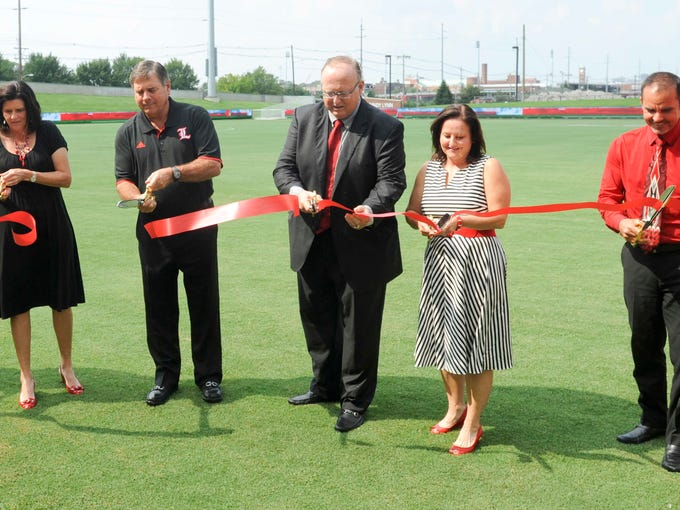 L-R: UofL Women's Soccer head coach Karen Ferguson Dayes, UofL Director of Athletics Tom Jurich, Dr. Mark Lynn, Dr. Lynn's wife, Cindy and UofL Men's Soccer head coach Ken Lolla cut the ribbon at the opening ceremonies of the Dr. Mark and Cindy Lynn (UofL) Cardinals Soccer Stadium. 25 August 2014