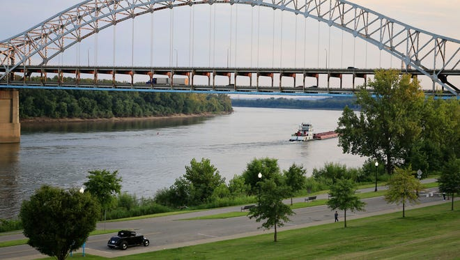 A vintage Ford coupe sits parked along the New Albany riverfront on a recent summer evening as a barge travels west along the Ohio River underneath the Sherman Bridge, New Albany's most iconic structure. New Albany's historic past has been embraced more in the past 10 years as more local businesses have opened up downtown. Aug. 21, 2015