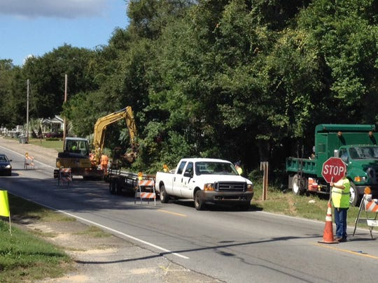 An Escambia County roads and bridges crew replacing