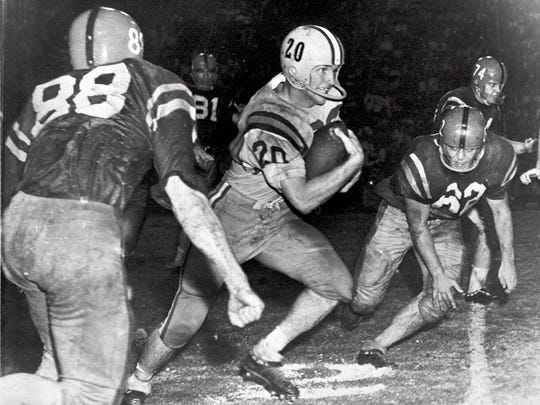 In this Oct. 31, 1959, file photo, Billy Cannon, LSU's All-America halfback, slips by tacklers at the start of an 89-yard punt return for a touchdown to help LSU beat third-ranked Mississippi, 7-3 in Baton Rouge. Cannon, the gifted running back who won the Heisman Trophy for LSU in 1959 with a memorable Halloween night punt return touchdown against Ole Miss, died Sunday, May 20, 2018. He was 80. LSU said Cannon, the school's only Heisman winner, died at his home in St. Francisville. The cause of death was not immediately known.