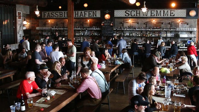 Patrons of the establishment enjoy seating with others at long tables at the Asbury Festhalle and Biergarten.