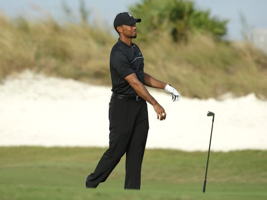 Tiger Woods tosses his club after hitting on the 16th