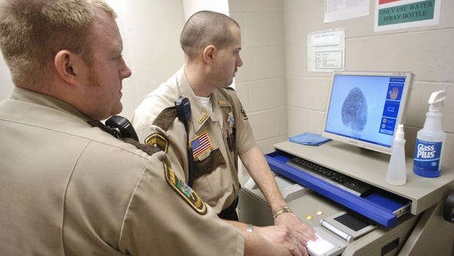 Stearns County officers work with a fingerprint scanning system.