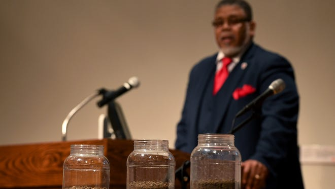 Pastor Daryll Coleman dedicates the soil dug from the lynching sites of three Black residents of Madison County, Eliza Woods, John Brown, and Frank Ballard, during a memorial for each of them, Friday, Feb. 23, at Jackson State Community College.
