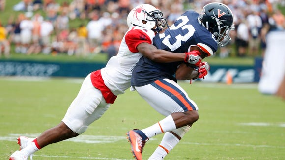 Sep 3, 2016; Charlottesville, VA, USA; Virginia Cavaliers wide receiver Warren Craft (23) catches the ball as Richmond Spiders defensive back Jarriel Jordan (1) tackles during the second half at Scott Stadium. Mandatory Credit: Amber Searls-USA TODAY Sports