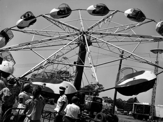 "There were many different rides and exhibitions to entertain people at the Ozark Empire Fair in August 1954.  Curious youngsters gathered to see how the ""Spitfire"" ride operated."