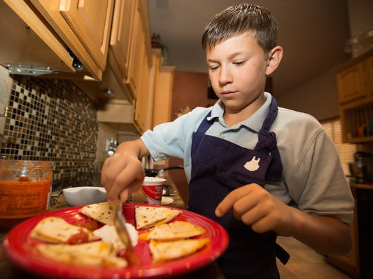McLean Knight prepares a cheddar cheese quesadilla with sour cream and salsa for an after school snack, August 24, 2016, at his home.