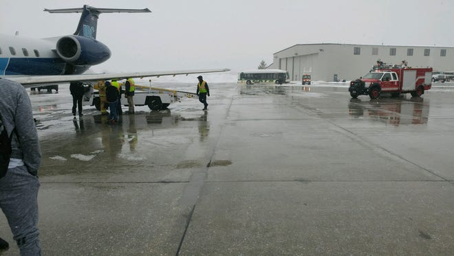 Emergency crews check a charter flight carrying the UVM men's basketball team, which returned from Tennessee on Thursday afternoon following its season-ending, NIT defeat. The smell of smoke in the back of the plane proved to be a false alarm.