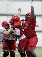 UL defensive lineman Sherard Johnson (97), right, participates in practice Tuesday, August 12, 2014, at the Leon Moncla Indoor Practice Facility in Lafayette, La.