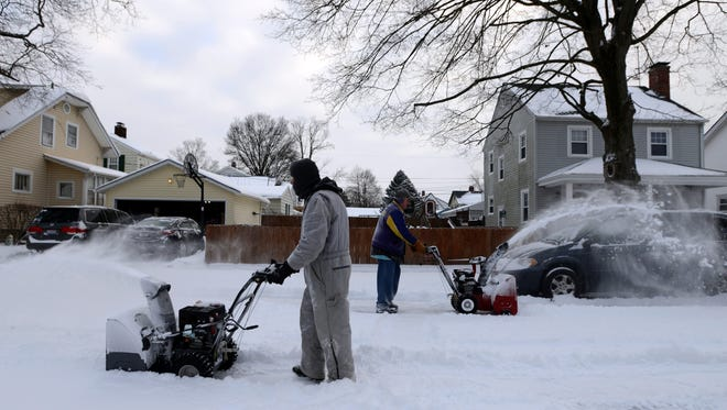 Bruce Allmon, left, and Brian Evans, right, use their snow blowers to clear their block of Oakwood Avenue between Fifth Avenue and King Street Saturday morning, Jan. 13, 2018, in front of their homes in Lancaster. A winter storm that moved through the area Friday night and Saturday morning left a layer of ice covered by more than five inches of snow.