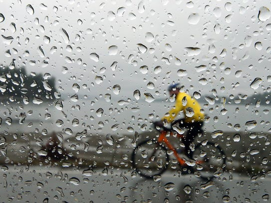 Raindrops coat a car window as a cyclist moves down