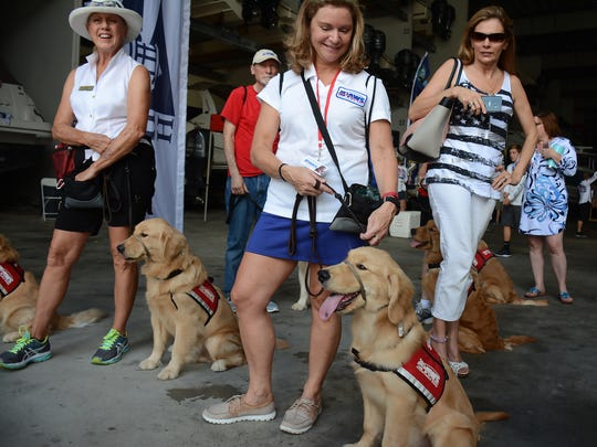 PAWS service dogs including Big Al, right with Peggy Lindenberg, are trained to assist wounded warriors. They came out to watch the soldiers come back from their day on the water.