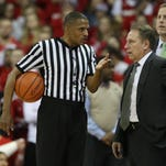 NCAA referee Ted Valentine discusses a point with Michigan State Spartans head coach Tom Izzo during the game against the Wisconsin Badgers.