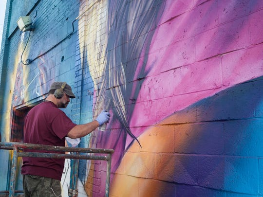 Detroit-based artist FEL3000FT   works on his Russell Street mural just before the start of the fourth annual Eastern Market After Dark event on Thursday, September 24, 2015. FEL3000FT was one of 45 artists contributing to the Murals in the Market festival which saw the completion of 40 murals around the Eastern Market District.
