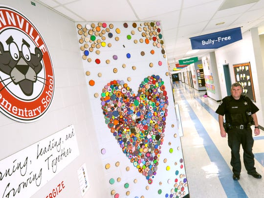 "Steven Cole, right, Anderson County Sheriff's Department school resource officer at Townville Elementary School, stands near ""Work of Heart"" in March 2017 at the school in Townville.  Students from kindergarten through sixth grade painted wood slices to piece together into two hearts displayed in the hallway, six-months after the shooting on the school playground."