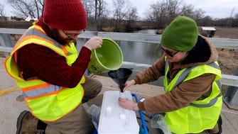 University of Wisconsin-Parkside student Josh Carlson (left) and Laura Schulz, water sampling project manager, collect water from the Root River at S. 60th St. in Franklin. Waukesha contracted with UW-Parkside to monitor river water quality this year as part of the city's $207 million project to switch to a Lake Michigan water supply in 2023.