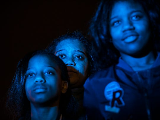 December 20, 2017 - (From left to right) Taniah Jackson, 12, stands with her mother Janet Jackson, and sister Tatiana Jackson, 14, as they observe the removal of Nathan Bedford Forrest's Confederate statue from Health Sciences Park on Wednesday night.