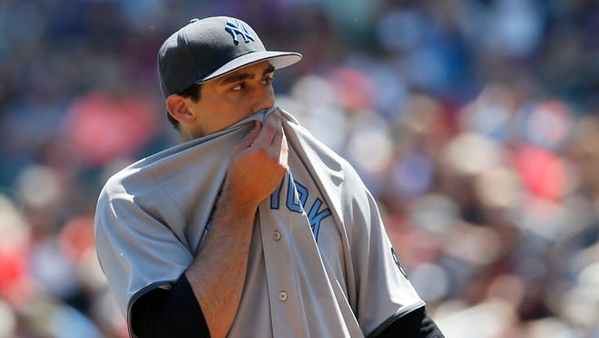 New York Yankees starting pitcher Nathan Eovaldi wipes his face after Minnesota Twins' Brian Dozier grounded into a fielder's choice during the first inning of a baseball game in Minneapolis, Sunday, June 19, 2016.