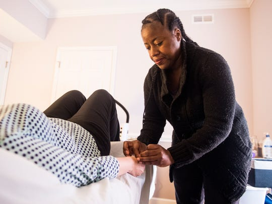Nikki Peoples, a military veteran and owner of Satori Acupuncture of Knoxville, performs acupuncture on a client at her business in Knoxville on Friday, May 25, 2018.