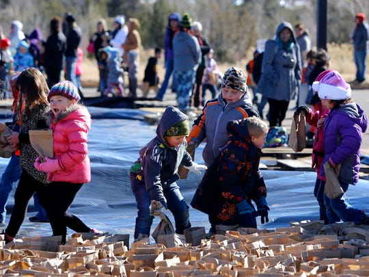 Students from Apache Elementary, Country Club Elementary and McKinley Elementary schools stack bags of luminarias on Tuesday at San Juan College in Farmington.