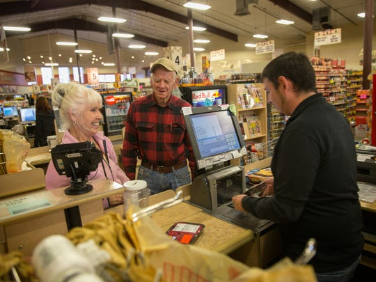 Customers Judy and Jack Richardson talk with cashier Tony Maestas Thursday in the checkout line at the Farmers Market in Flora Vista.