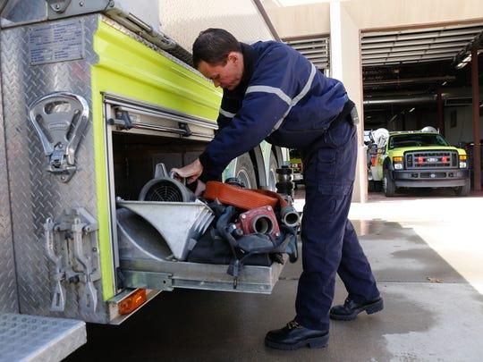 Engineer Ian Rutter examines equipment on a fire truck