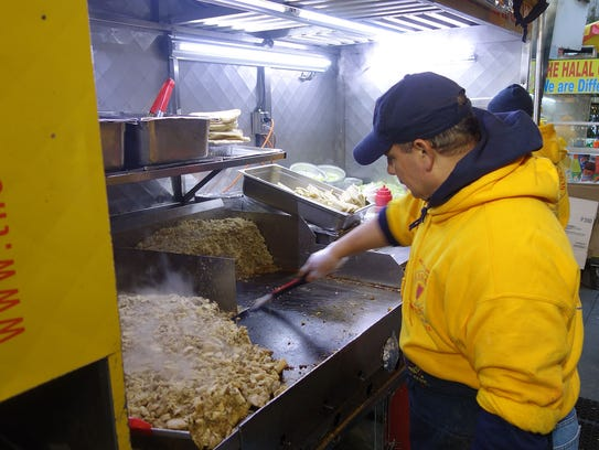 A griddle man preps chicken for one of The Halal Guys'
