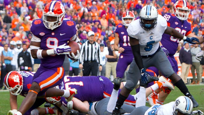 Clemson Tigers running back Travis Etienne avoids the tackle by Citadel Bulldogs defensive back Carl Cunningham Jr. and scores a touchdown during the third quarter at Clemson Memorial Stadium.