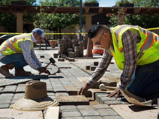 """Employees of Landscape and Design Center Adrian Sierra, right, and Adolfo Rios place pavers around artist Tony Pennock's """"Rio Grande Time"""" sun dial on Friday, Sept. 9, 2016, at the Plaza de Las Cruces. The official plaza opening is scheduled for Saturday, Sept. 17, 2016."""
