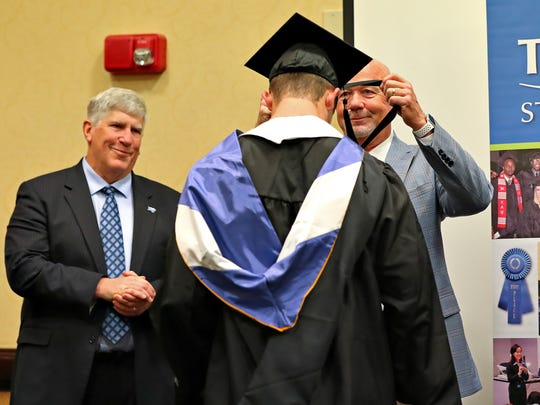 MTSU coach Rick Stockstill bestows a stole around the neck of Brent Stockstill, his son and the team's starting quarterback, during a special graduation ceremony at the Embassy Suites hotel in Montgomery, Ala., on Dec. 15, 2017.