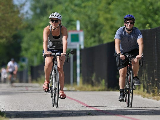 Two cyclists brave the heat along the Monon Trail approaching