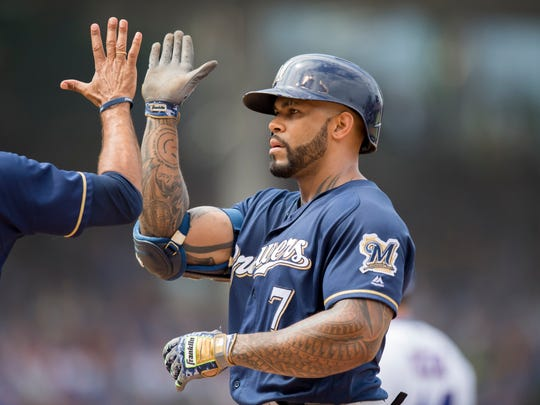 Brewers first baseman Eric Thames  celebrates with first base coach Carlos Subero after hitting an RBI single in the fourth inning.