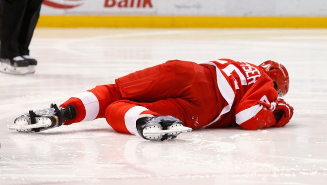 Red Wings defenseman Danny DeKeyser (65) lies on the ice after being hit by a Ottawa Senators shot in the third period of the Wings' win Wednesday at Joe Louis Arena.