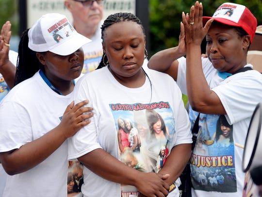 Yolanda Clayton-Woods (center), of Vero Beach, is comforted