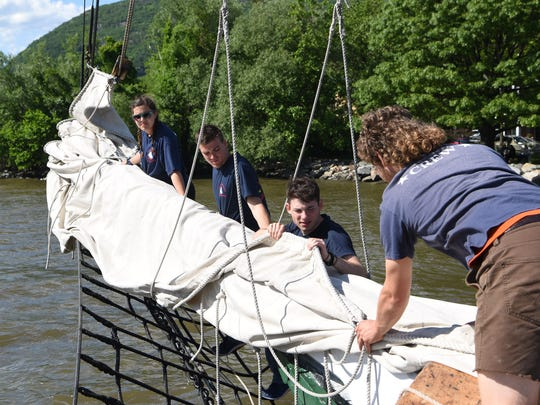 Crew members and volunteers furl the jib on the sloop Clearwater while docked in Cold Spring. From left to right: Marilia Andrade, Brandon Bordelon, Ira Moll, and Dylan Kane.
