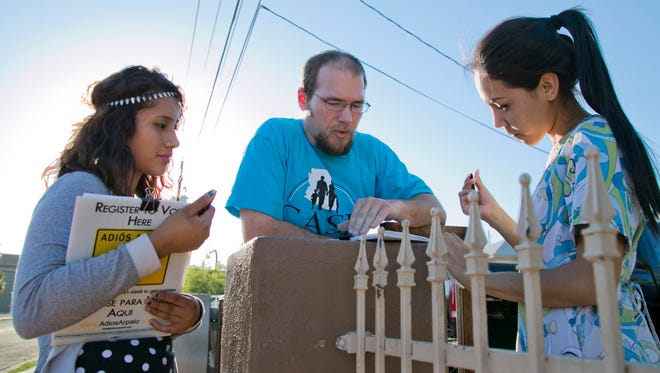 Yaraneth Marin (left) and Jason Bates, volunteers for Central Arizonans for a Sustainable Economy, talk to Hilda Chavez outside her house during a recent voter-registration drive aimed at low-income, Latino and single-mother voters in Phoenix.