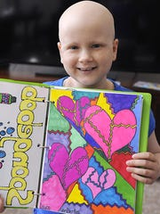 Laura VanDerBos, 12, shows some of her artwork at home in Grand Ledge June 8. Adding to her sketch book is something she does often. Colorful hearts are one of things she loves to draw.