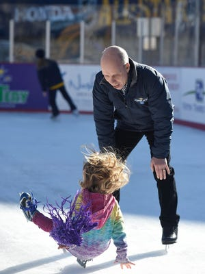 Scott Hamilton can't stop Hanna Madson, 3, from falling at the Bridgestone Winter Park outdoor ice rink in Walk of Fame Park on Thursday in Nashville.