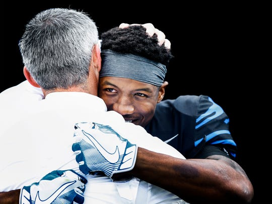 Memphis receiver Anthony Miller hugs head  coach Mike