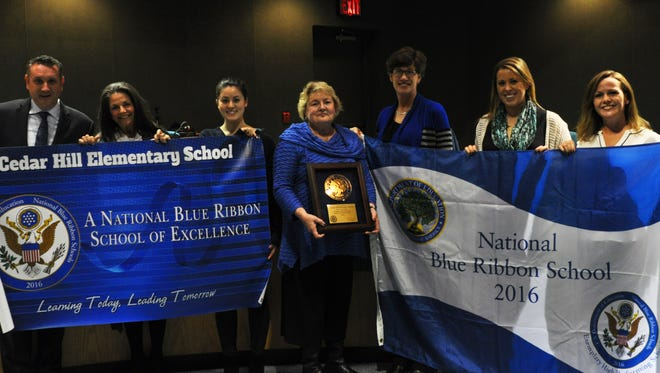 Cedar Hill Elementary in Montville was chosen for the 2016 National Blue Ribbon School award. Principal Dr. Michael Raj, Dr. Cathy Lundquist, Katelyn Kung, Anne Fisher, Janice Koch, Stephanie Malgieri and Maureen Livera show off banners given to the school.