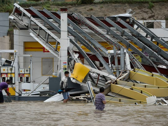 People walk next to a gas station flooded and damaged
