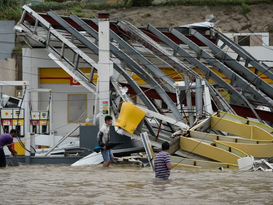 People walk next to a gas station flooded and damaged by the impact of Hurricane Maria, which hit the eastern region of the island, in Humacao, Puerto Rico, Wednesday, September 20, 2017. The strongest hurricane to hit Puerto Rico in more than 80 years destroyed hundreds of homes, knocked out power across the entire island and turned some streets into raging rivers in an onslaught that could plunge the U.S. territory deeper into financial crisis.