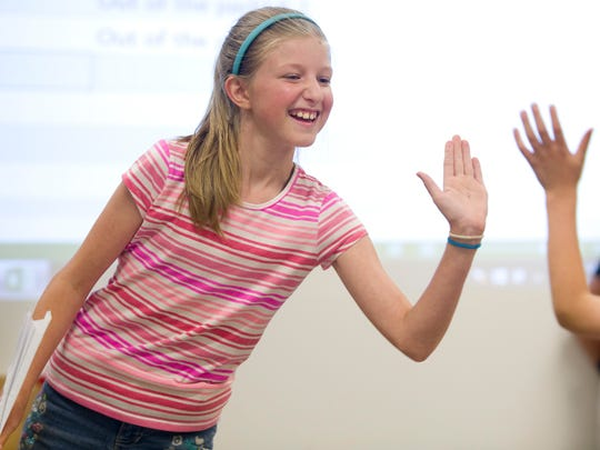 Christina Payne, 10, gives her little brother, Matthew, 6, a high-five after he successfully flew his paper airplane at the Evansville Museum's Paper Airplane Day in the summer. The museum is hosting another Airplane Day this weekend.