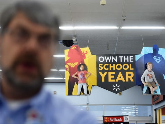 A back-to-school sign hangs behind Boyce Smith, Walmart's
