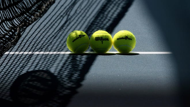 A group of tennis balls sits on the court prior to a match at the Australian Open