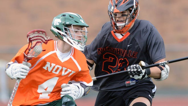 Novi's Anthony Zugaro (right) keeps possession while trying to fend off Northville's Connor Wright.