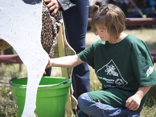 Kelsey Geiskell, 9, participates in the Cow Milking